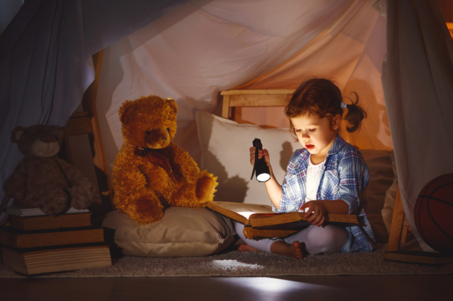 child girl with a book and a flashlight and teddy bear before going to bed